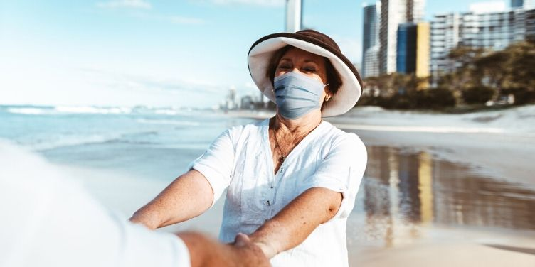 Woman on beach wearing face mask