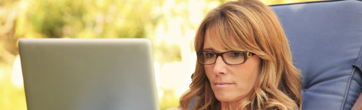Woman in glasses reading on a laptop