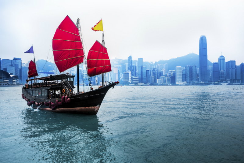 A junkboat sailing down a Hong Kong river with the skyline looming in the background