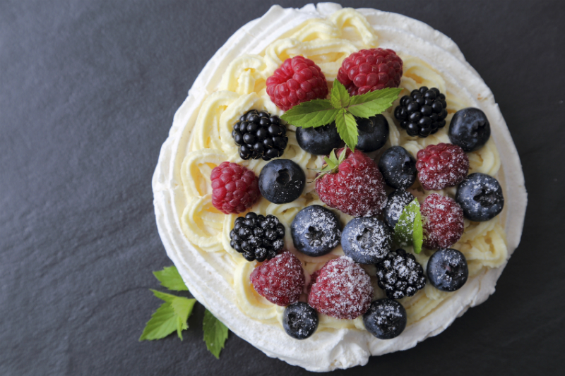 A fresh berry pavlova with icing sugar on top