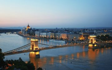 A view of the majestic Budapest skyline by night, the river and the bridge
