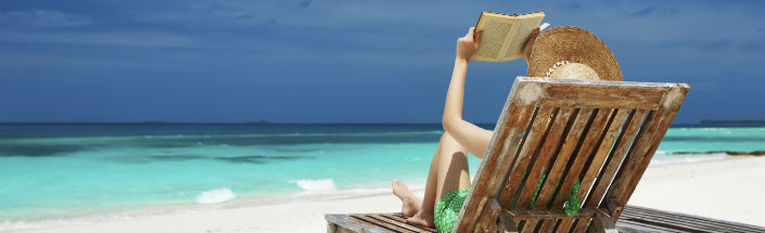 A relaxed woman reading a book in a deckchair on the beach