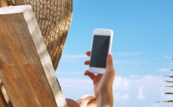 Woman using a mobile phone on a sun lounger