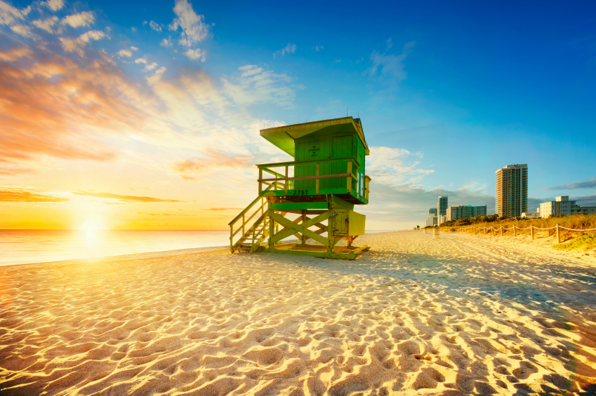 Miami South Beach sunrise with lifeguard tower and coastline with colorful cloud and blue sky.