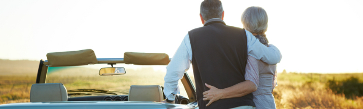 Mature couple enjoying sunset while standing next to car