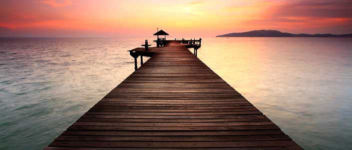 A wooden bridge jutting out into an alluring sea at sunset
