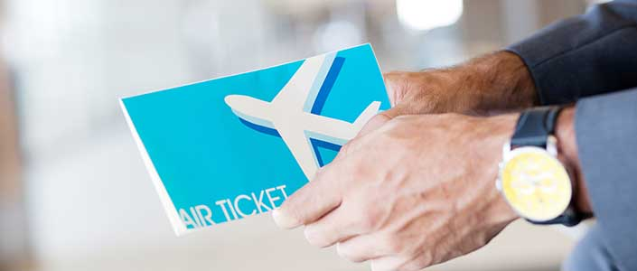 A man's hands holding an air ticket booklet