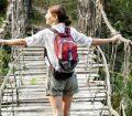 Solo woman traveller crosses a rope bridge