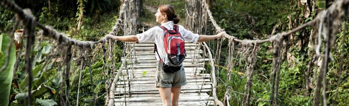 Solo woman traveller crosses a rope bridge