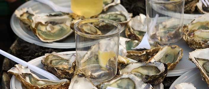Several plates of fresh oysters and glasses of white wine.