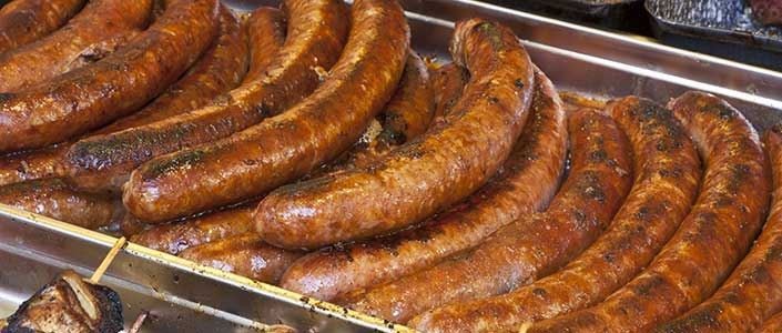 A photo of some tasty looking sausages in a roasting dish.