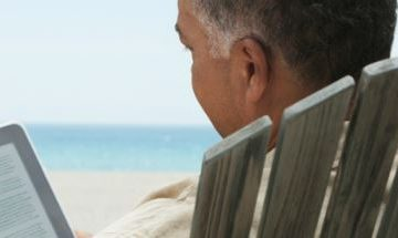 Mature man reading an ebook on the beach
