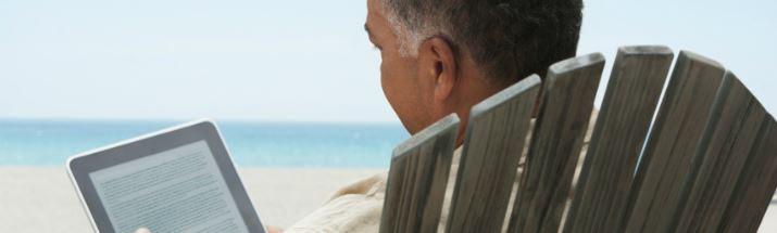 Mature man reading an ebook on the beach