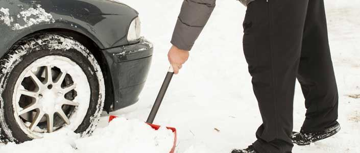 Man using shovel to dig car out of snow