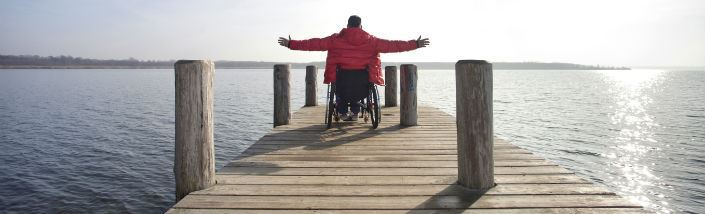 A man in a wheelchair at the end of the pier