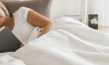 Woman reading comfortably in bed