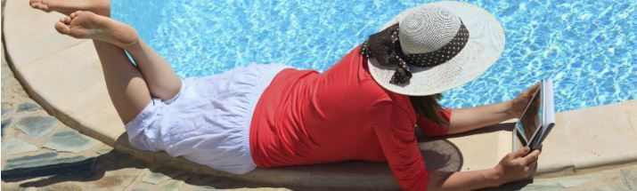 Woman with an ebook reader poolside