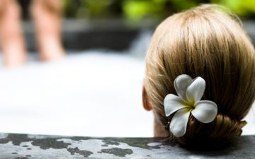 A woman with a flower in her hair relaxing on the side of a jacuzzi