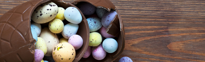 A Large chocolate easter egg spilling out smaller mini easter eggs in pastel colours