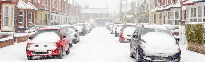 Cars lining a snowy street