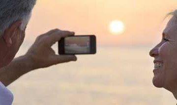 A couple looking at a phone screen in front of a sun setting