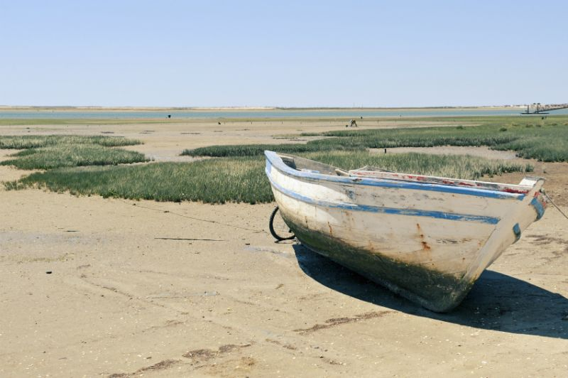 A boat on the sandy beach of Faro Island, Portugal