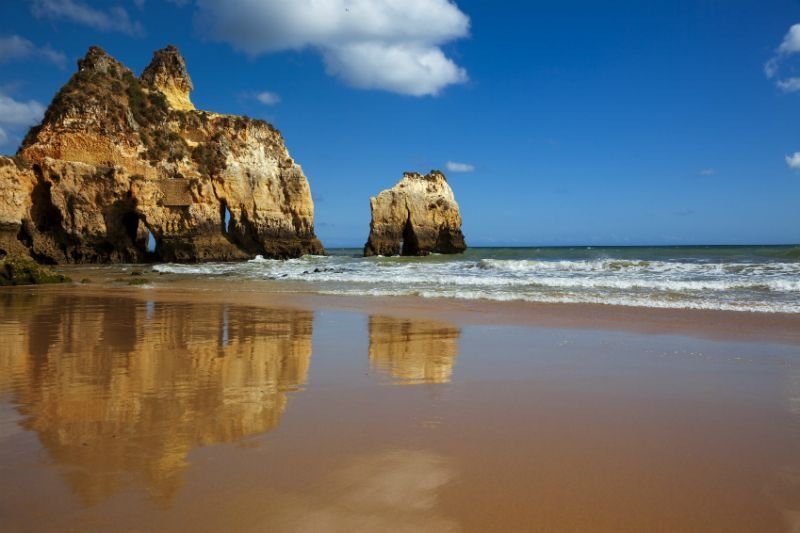 Rocky coves against the sun at Praia Tres Irmanos, Portugal