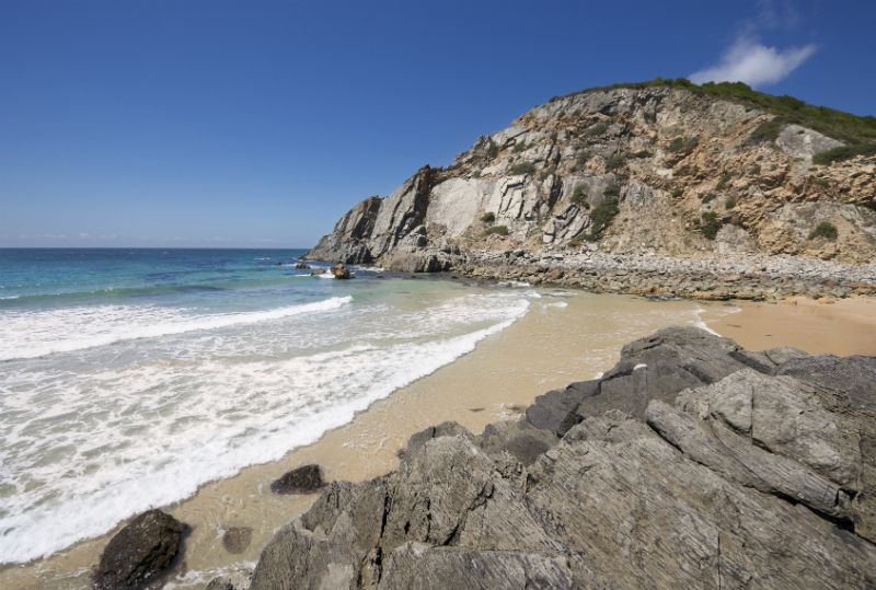Guincho beach with calm waves surrounded by boulders and cliffs