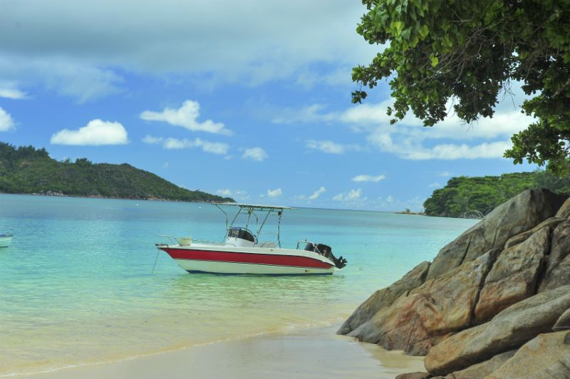 Boat docked by a beach in the Seychelles