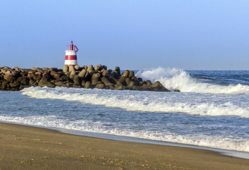 Tides crashing on the rocks at Ilha de Tavira Beach, Portugal