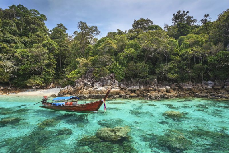A boat on the clear waters of Koh Lipe Beach, Thailand