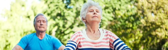 Mature people doing yoga on holiday