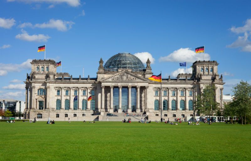 Reichstag building with people outside and German flags, Berlin