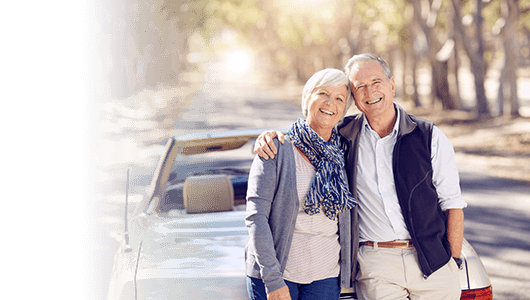 Osteoporosis travel insurance banner - senior couple leaning on a car