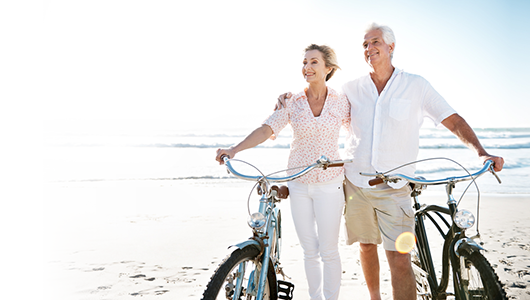 Senior couple riding bikes on the beach