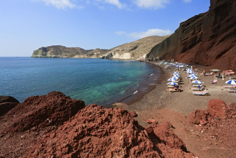 Sunbathers under umbrellas on the red beach in Santorini, Greece