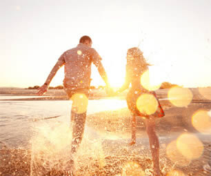 Couple in the waves on a beach at sunset