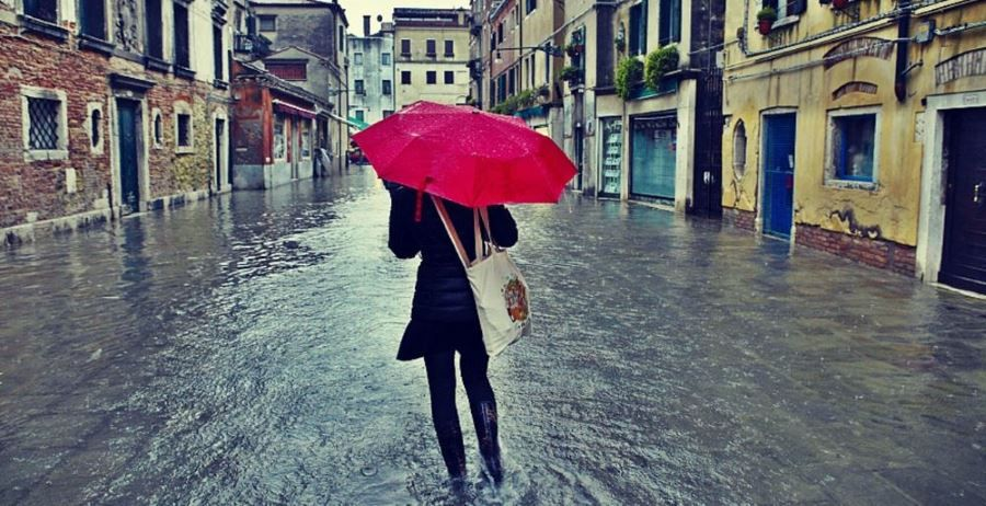 A woman walking through the flooded streets of Venice, protected by a red umbrella