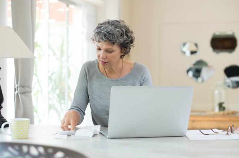 Mature woman checking bills