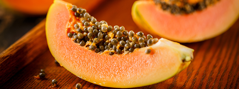 Halved and whole papaya fruits on the background