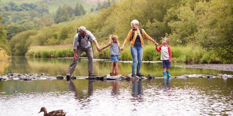Grandparents and grandchildren crossing river
