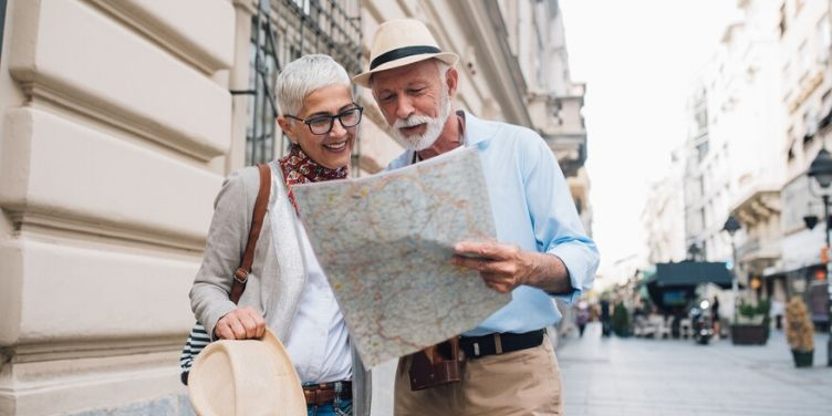 senior couple looking at map in city