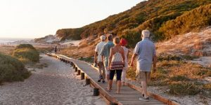 group of senior friends walking towards the beach