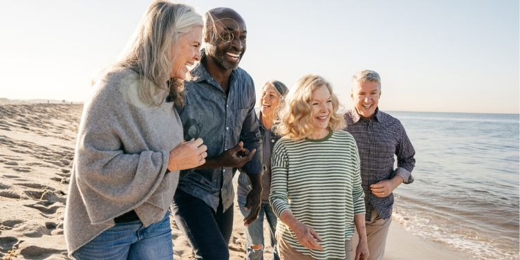 group of seniors laughing on beach