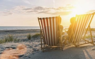 couple on beach in deck chairs at sunset