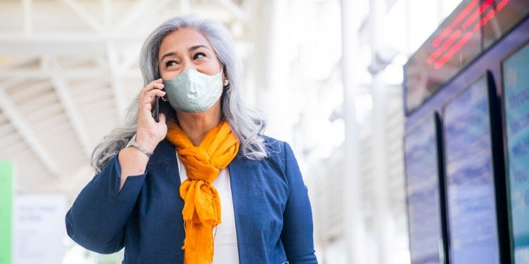 Woman walking through airport wearing face mask